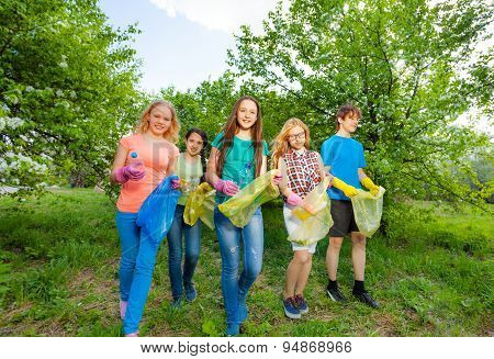 Teenagers wear gloves and carry garbage bag