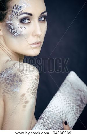 portrait of pretty young woman with creative make up like a snake, fashion victim with python skin c