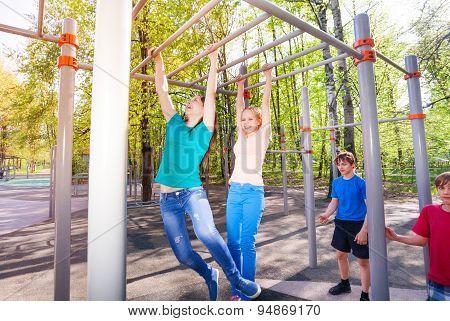 Teenagers hang on horizontal bar at sports ground