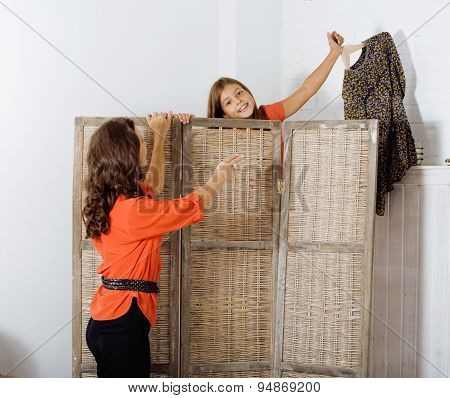 happy mother with daughter trying on dresses at home