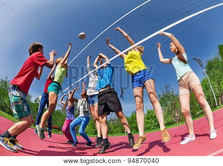 View from below of teens playing volleyball