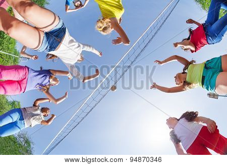 View from below of kids playing volleyball