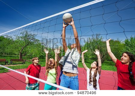Teen girl catches the ball during volleyball game