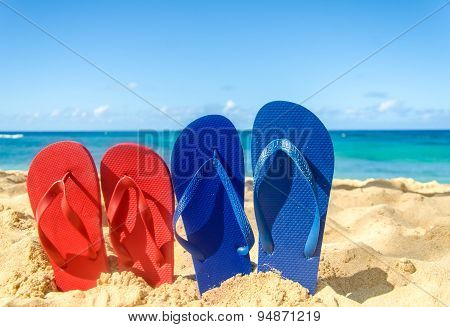 Blue And Red Flip Flops On The Sandy Beach