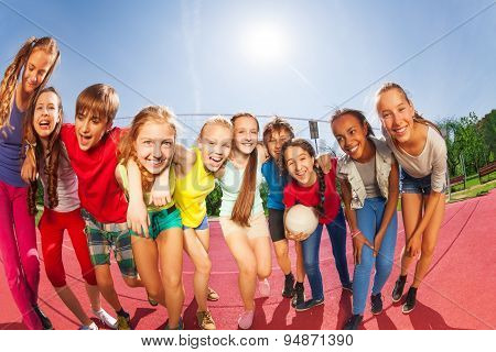 Row of happy teens standing on volleyball court