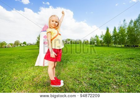 Girl wears rocket toy on shoulders holding arm up