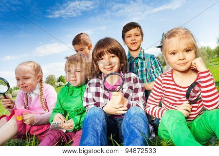 Cute children sitting on grass with magnifier