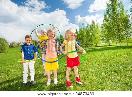 Happy children holding hula hoops during exercises