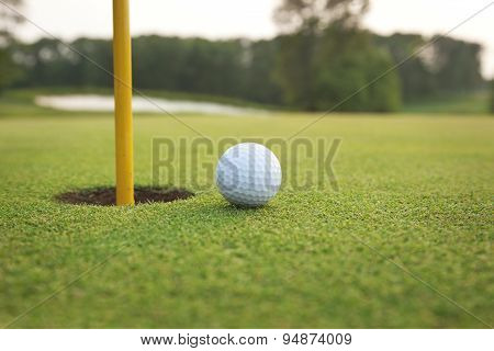 Close Up Of Golf Ball On A Green Near Hole With Pin