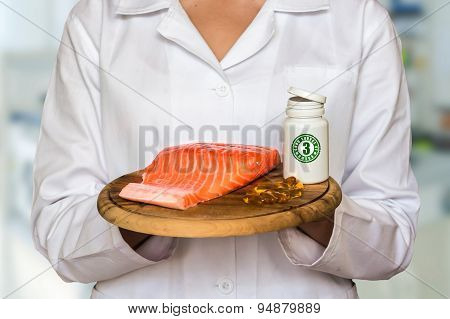 Young Doctor Holding Salmon On A Wooden Plate And Bottle Of Pill