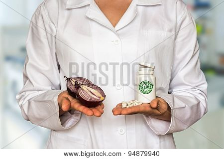 Young Doctor Holding Two Halves Of Onion And Bottle Of Pills Wit