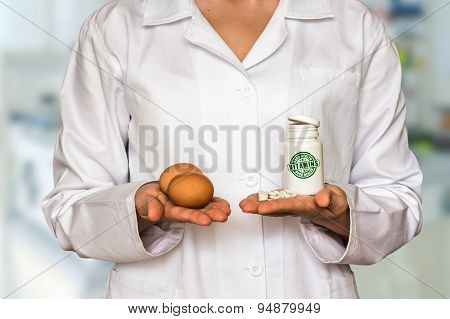 Young Doctor Holding Eggs And Bottle Of Pills With Vitamins And