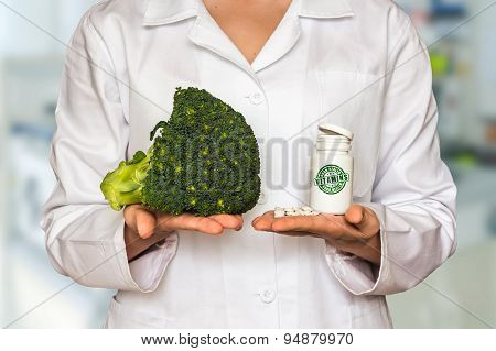 Young Doctor Holding Fresh Broccoli And Bottle Of Pills With Vit