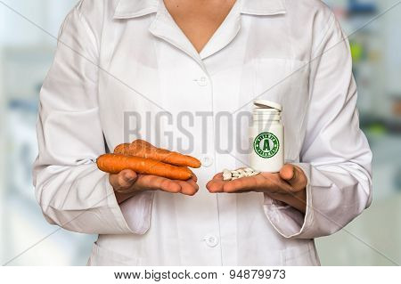 Young Doctor Holding Carrots And Bottle Of Pills With Vitamin A