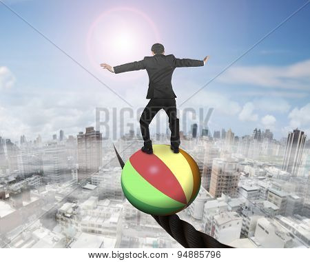 Businessman Standing On Ball Balancing On Wire