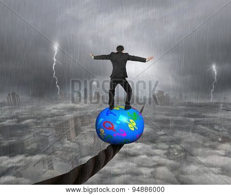 Businessman Standing On Ball And Balancing On Wire
