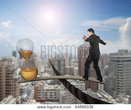 Businessman And Hourglass On Wood Board Balancing On Wire