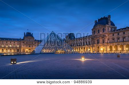 The large glass pyramid and the main courtyard of the Louvre Museum