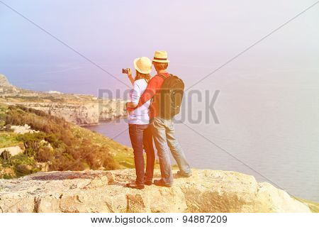 young couple hiking in mountains making photo