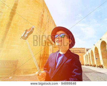 little boy taking selfie stick picture while travel in Europe, Malta