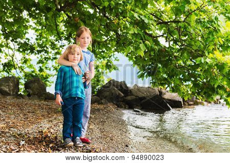 Two cute kids playing outdoors by the lake, big sister hugging little brother