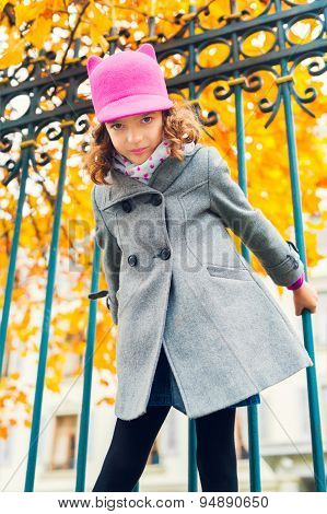 Lovely little girl playing outdoors, wearing grey coat and pink hat with ears