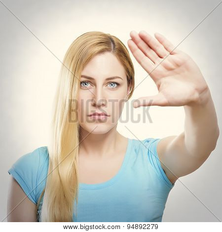 Attractive Blonde Woman With Her Hand Holding It At Arm's Length