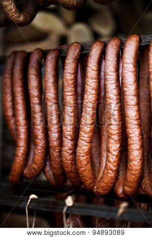 Traditional food. Smoked sausages meat hanging in domestic smokehouse.