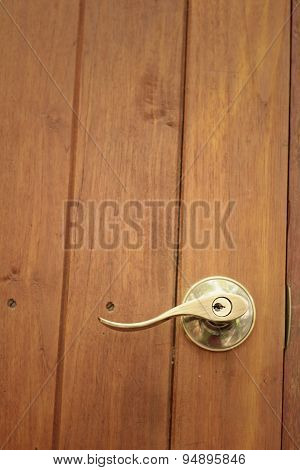 Door Handles Of A Brown Wooden Door.