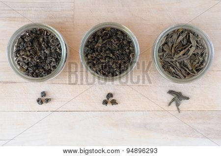 Assortment of dry green tea leaves in jars