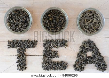 Assortment of dry green tea leaves in jars with letters made of tea leaves