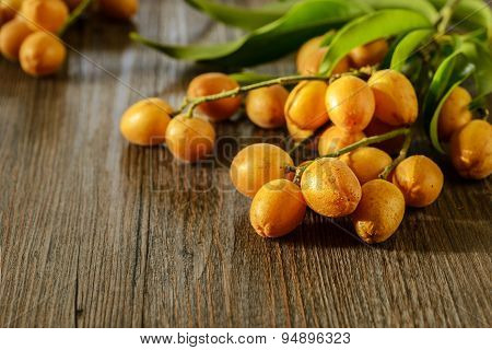 Wampee Fruit On The Wooden Board