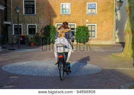 The Woman And Little Girl Riding A Bicycle In The Dutch City Meerkerk, Netherlands