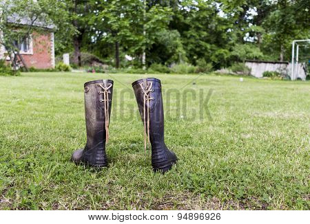Two rubber boots on a green lawn near red house in farm
