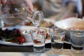 picture of vodka  - Person pouring vodka into glasses in the pub - JPG