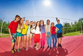 pic of volleyball  - Row of teenagers who stand on volleyball game court holding ball during summer sunny day - JPG