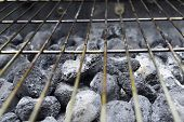 foto of briquette  - Charred charcoal briquettes waiting to be lit beneath an old grill grate - JPG