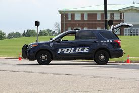 image of police  - A police department SUV parked on a road in front of a building - JPG