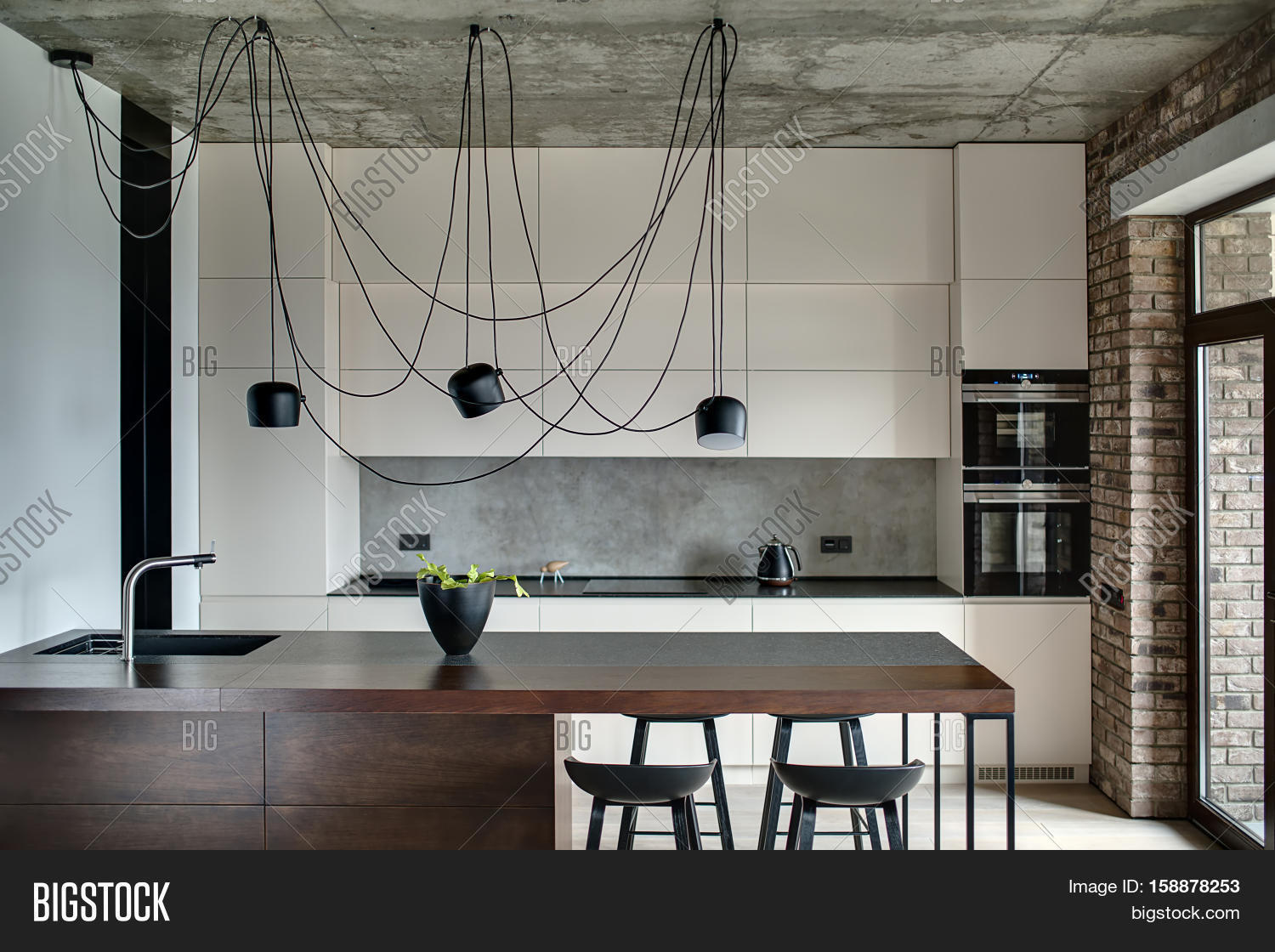 kitchen in a loft style with concrete and brick walls there is a kitchen island