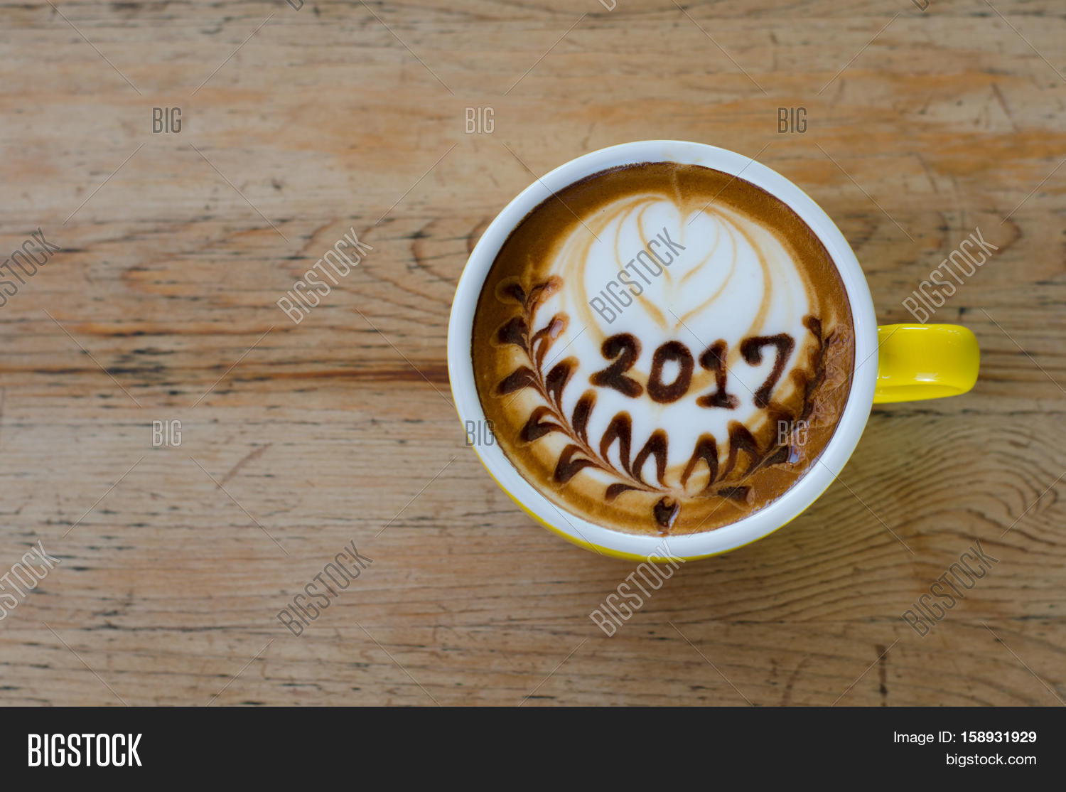 hot coffee with foam milk art 2017 on wooden table stock photo