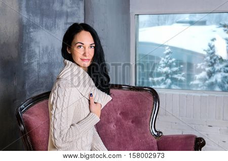 Portrait of young beautiful brunette woman. Winter wiew in window on a background with pines and snow