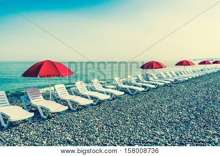 Beach chairs or beds and sun red umbrellas on the beach near sea - retro style