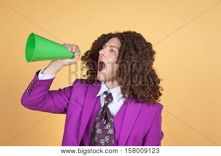 Caucasian man with afro wearing Purple Suit shouting from a cone standing in front of yellow background