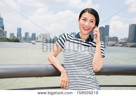 Happy young woman using mobile phone while leaning on railing against cityscape