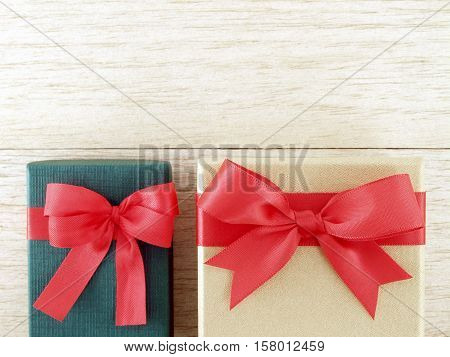 two gift boxes (green and golden) with red ribbon bow on wooden floor, top view