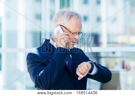 business, technology, time, punctuality and people concept - senior businessman calling on smartphone an looking at wristwatch in city