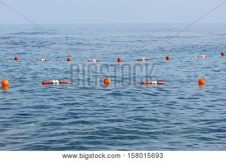 Orange buoys at safe swimming zone in the sea