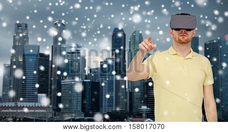 technology, augmented reality, winter, christmas and people concept - young man with virtual headset or 3d glasses playing game over singapore city skyscrapers background and snow