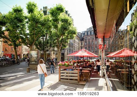 STRASBOURG FRANCE - JUL 4 2016: Woman walking near Chez Marco's Bar Cintra in central Strasbourg waiting for customers on a bright sunny day for best cocktails and alcohol or sweet beverages inside or on the best terrace
