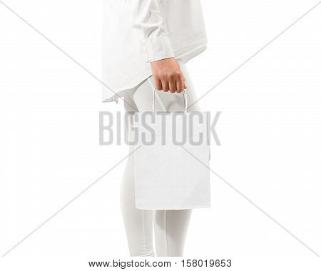 Blank white craft paper bag mockup holding hand, clipping path. Woman hold textured package mock up.